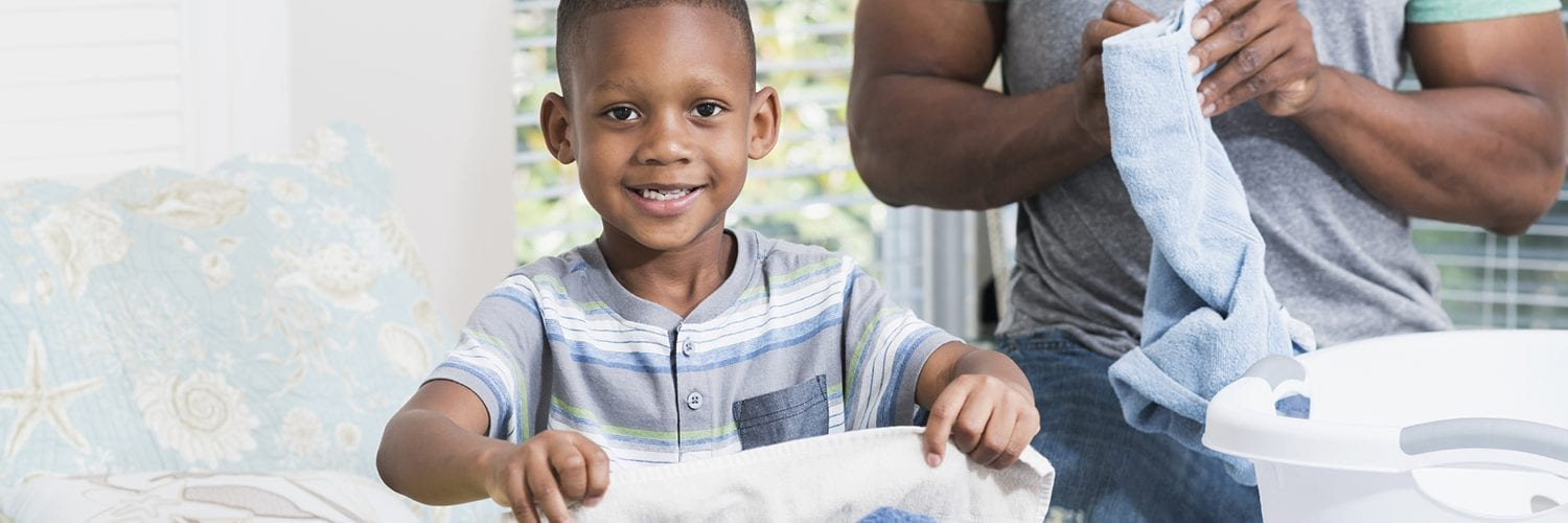 little boy helping his father fold laundry