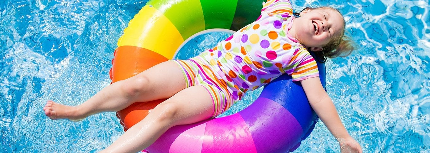 child in swimming pool playing with colorful inflatable ring