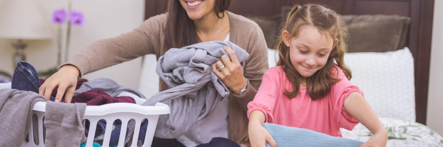mother cheerfully folding clothes with her daughter