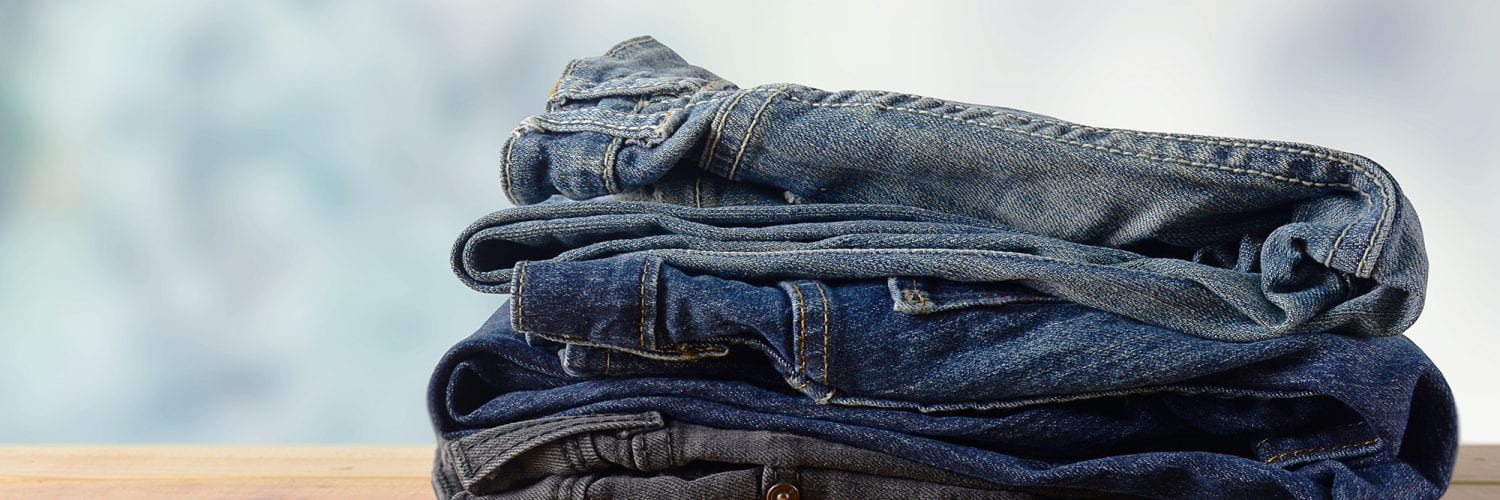 stack of jeans on wooden