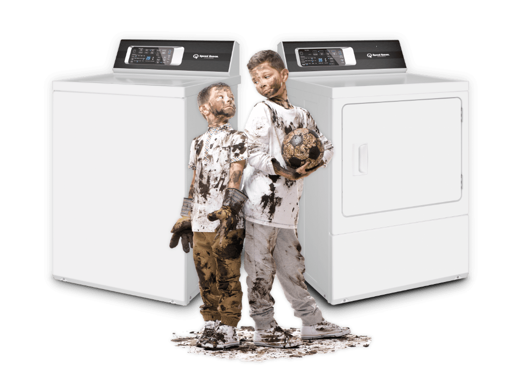 two boys in dirty soccer clothes in front of washer and dryer
